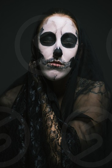 woman in painted skull face makeup and black alce top photo