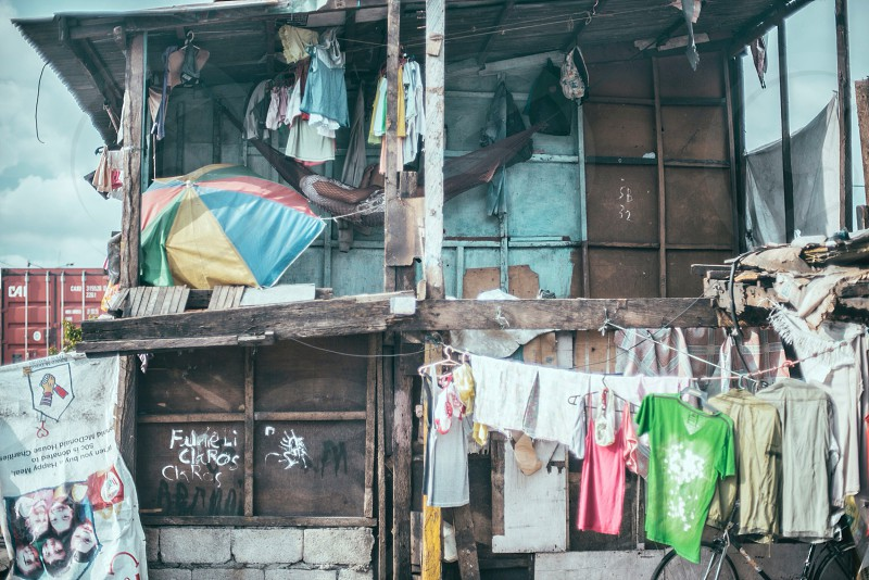 green pink grey and white shirts hanged and brown wooden house photo