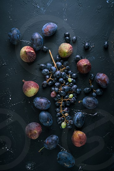 Bunch of blue grapes figs on dark blue background. Vertical image top view. photo