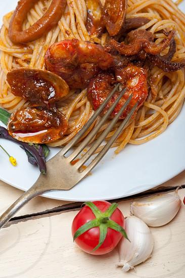 Italian seafood spaghetti pasta on red tomato sauce over white rustic wood table photo