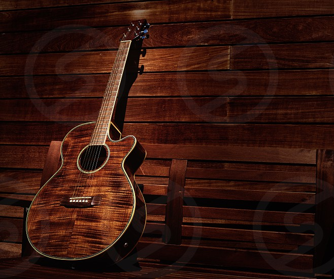 acoustic brown guitar in a wooden stripes wooden wall monochromatic photo