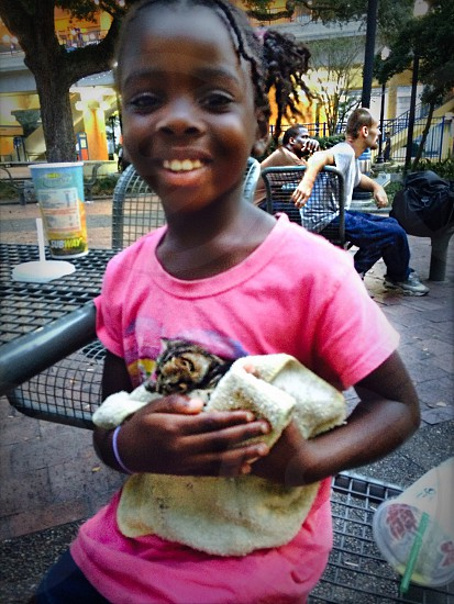 While downtown Jacksonville florida this beautiful spirited little homeless girl made sure to nurture her kitten she found on the side of the road.  We had brought food toys clothes and a ton of other things to help them. But this little girl sat away from the group of 20 or so people just to protect her kitten.  photo