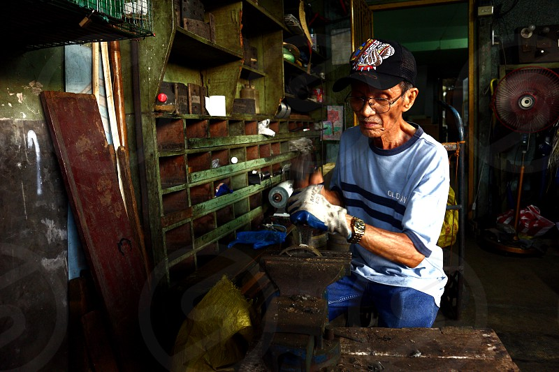 ANTIPOLO CITY PHILIPPINES - MAY 21 2019: A brake relining shop worker removes old and worn out lining from an old brake shoe of a motorcycle. photo