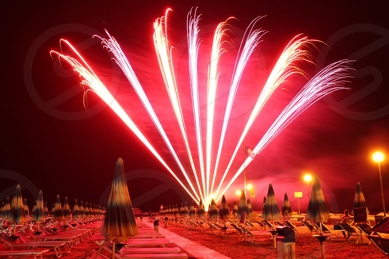 photo of red and white fireworks near yellow and purple umbrella and chair lounge during nighttime photo