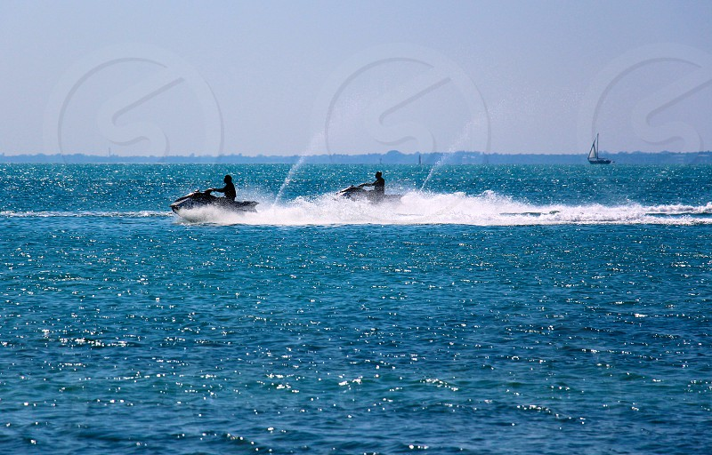 2 people riding jetski on blue water during daytime photo