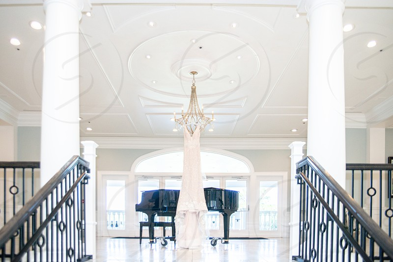 White wedding dress handing from chandelier in ballroom over piano photo