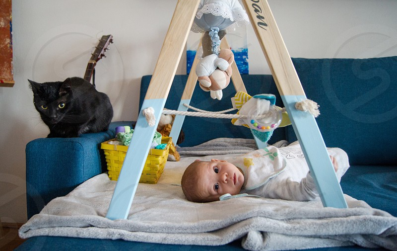 Baby boy playing with a baby gym. photo