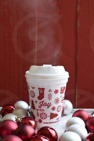 A Christmas coffee cup from Dunkin Donuts surrounded by Christmas ornaments photo