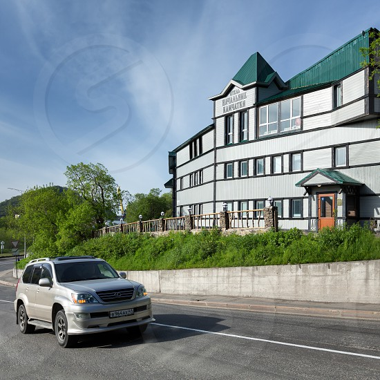 PETROPAVLOVSK-KAMCHATSKY CITY KAMCHATKA PENINSULA RUSSIA - JUN 16 2017: Summer view of building of Hotel Chief of Kamchatka (Nachalnik Kamchatki) and road near hotel with rides car in sunny weather photo