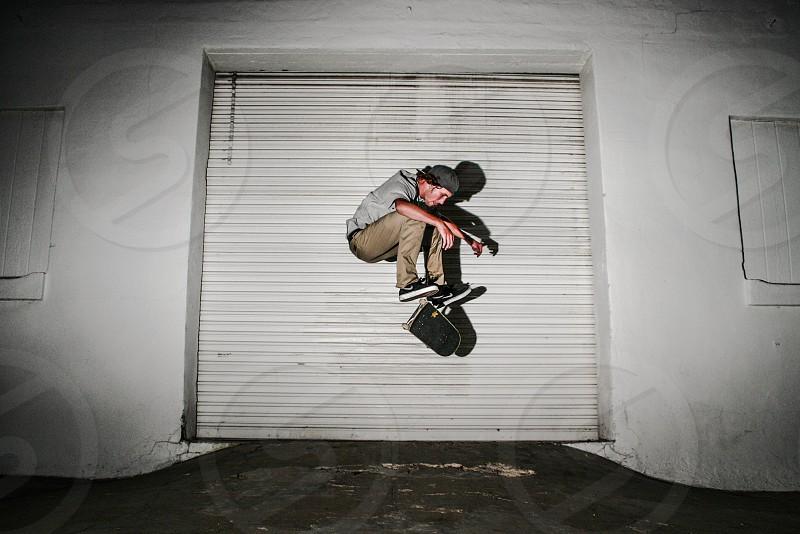 man in grey hoodie and brown pants doing skateboard stunts photo