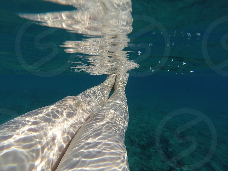 Closeup shot of woman's legs under the sea against the clear green background photo