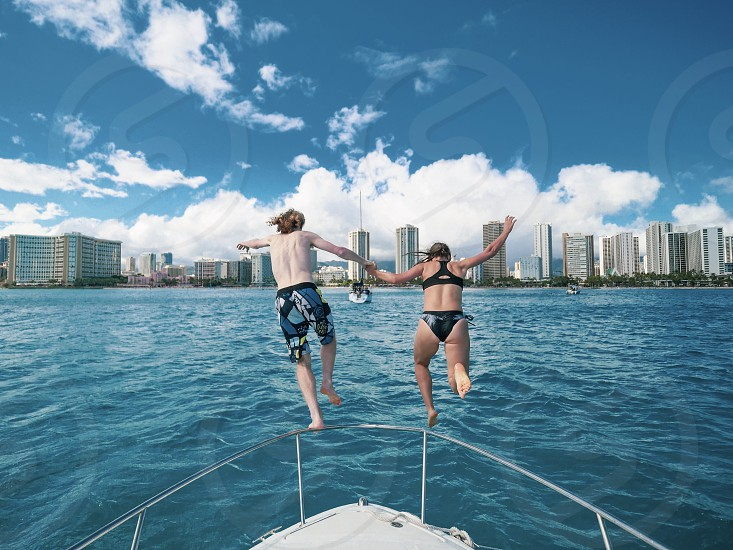 Couple holding hands jumping off a boat in the ocean adventure love lifestyle romance  photo