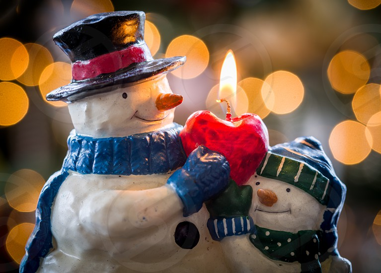 Snowmen candles with out of focus lights of christmas tree behind photo