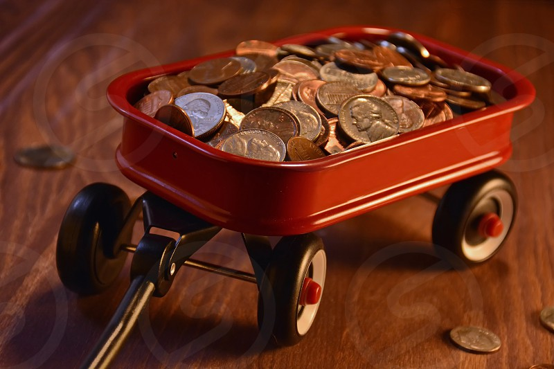 Child's little red wagon full of coins photo