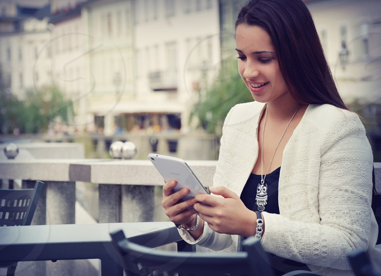 Young girl seating in a city cafe outside holding tablet and looking at it. photo