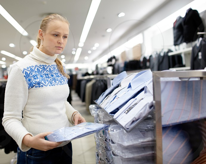 Young woman is thinking what shirt will be the best for her boyfriend. photo