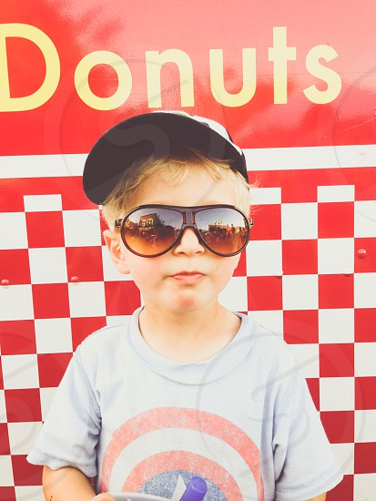 fair carnival boy child youth sunglasses donuts treats concession hat cap shades retro vintage checker red yellow blue tint blonde  photo