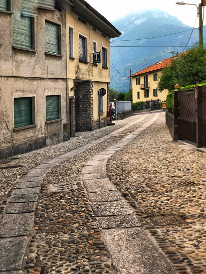 A small cobblestone street in an old Italian town with mountains in the background. photo
