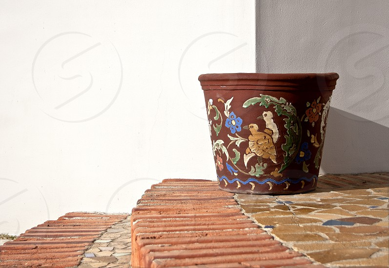 Painted clay pot on brick steps in front of white wall. photo