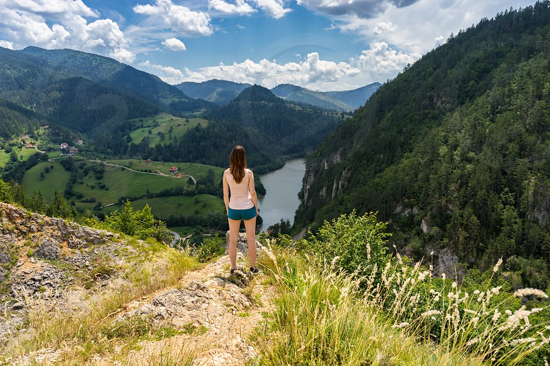 Young tourist woman stand in beautiful place in Tara national park in Serbia on point with scenic view on mountain lake and looks forward from a height photo