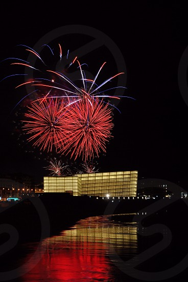 red fireworks display above white building across body of water photo