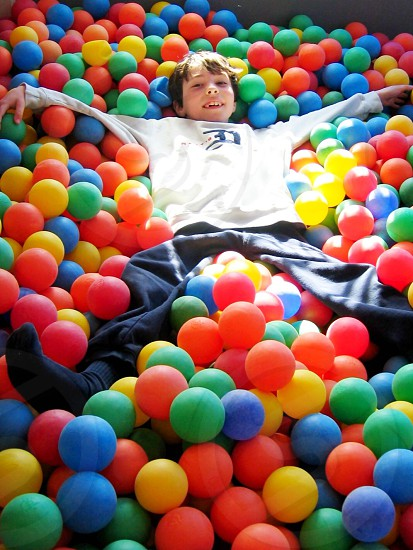 boy in white long sleeved shirt lying on red blue green and yellow balls photo