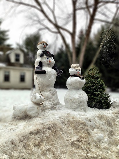 3 white snowman figure beside green chirtmas tree photo