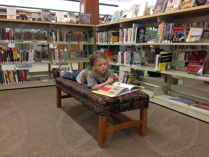 Girl reads books in library photo