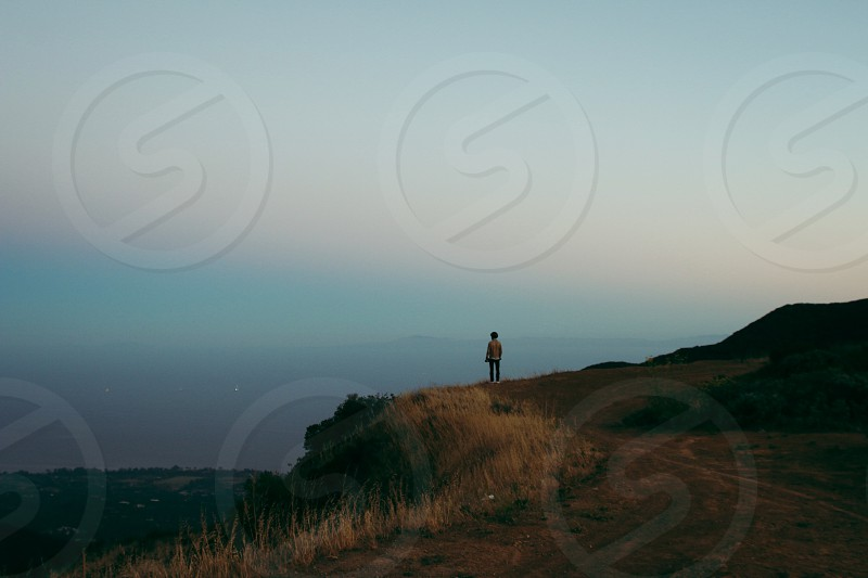person standing on top of hill under white skies photo