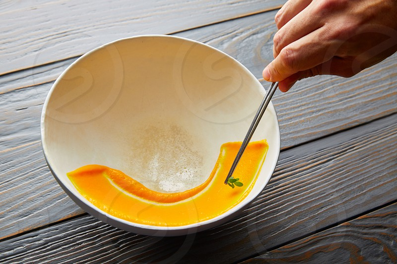 creamy carrot cream painted on white bowl while chef preparation process photo