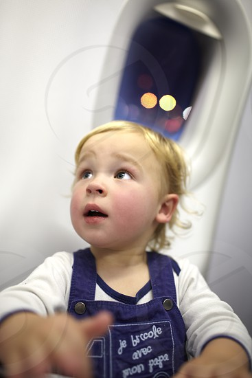 Young passenger in the plane. Beautiful bokeh lights in the porthole. photo