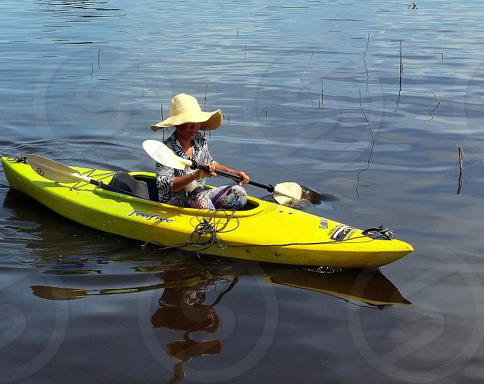 person in yellow sunhat riding on yellow kayak photo