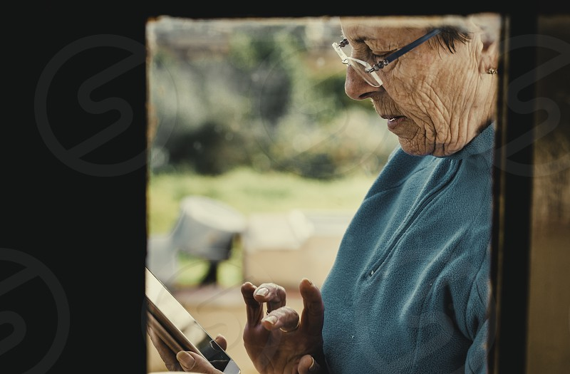 Shot of an attractive old woman standing behind a glass window while using her mobile phone and text messaging photo