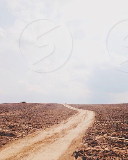 winding dirt trail across desert under grey sky photo