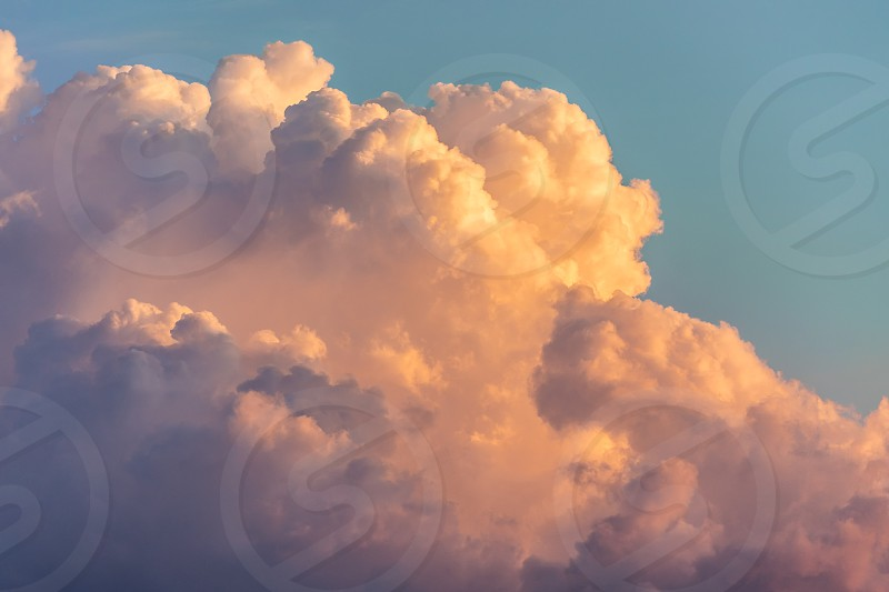 Close up view of beautiful colored dramatic cumulus fluffy clouds on blue sky at sunset background photo