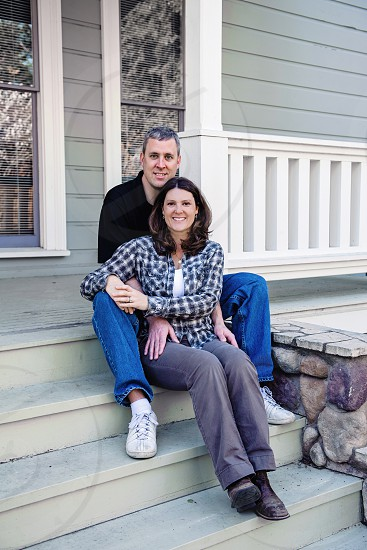 Caucasian man and woman sitting on front steps of Victorian house photo