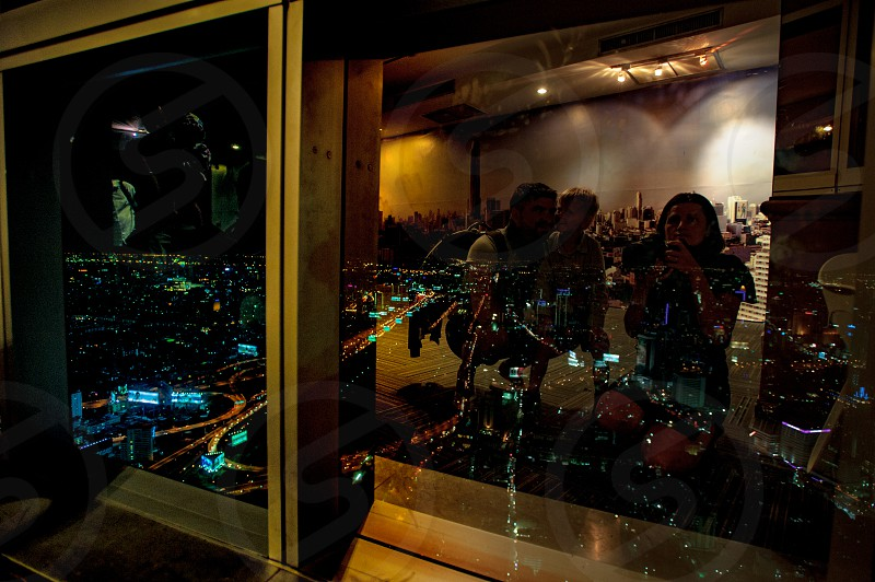 Family portrait reflected on a window. Watching Bangkok at night. View from a skyscraper photo