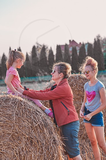Mother and her daughters teenage girl and her younger sister playing together on hay bale outdoors spending vacations in the countryside. Candid people real moments authentic situations photo