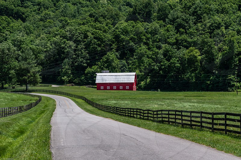 winding country road rail fence red barn pasture western north carolina green grass photo