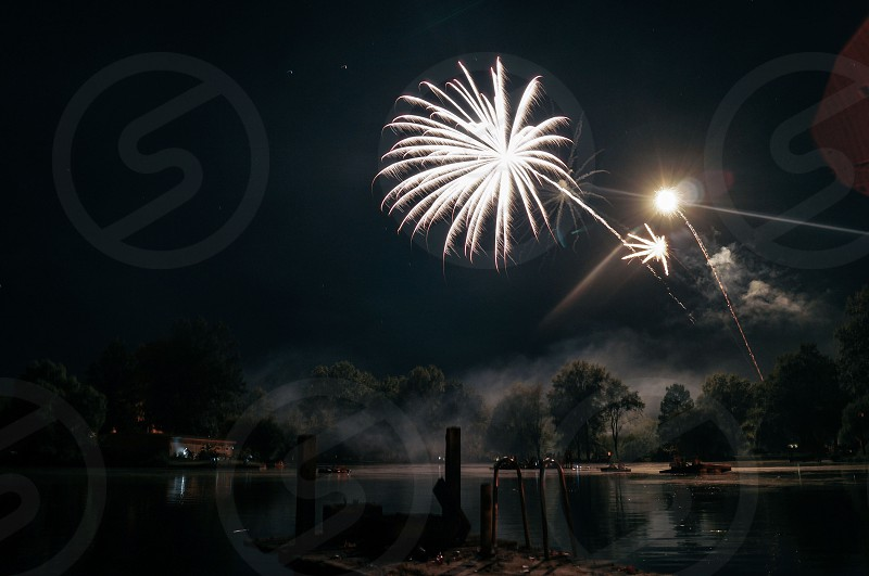 brocade fireworks above calm water surface during nighttime photo