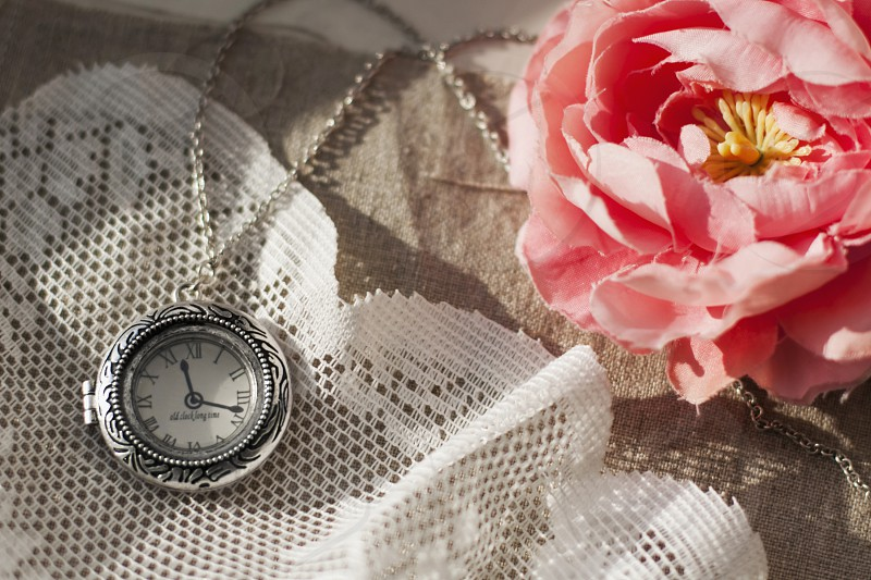 round silver pocket watching lying on white lace next to pink rose photo