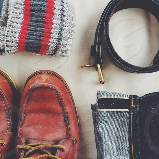 brown leather shoesblack beltgrey and red socks and blue denim jeans photo