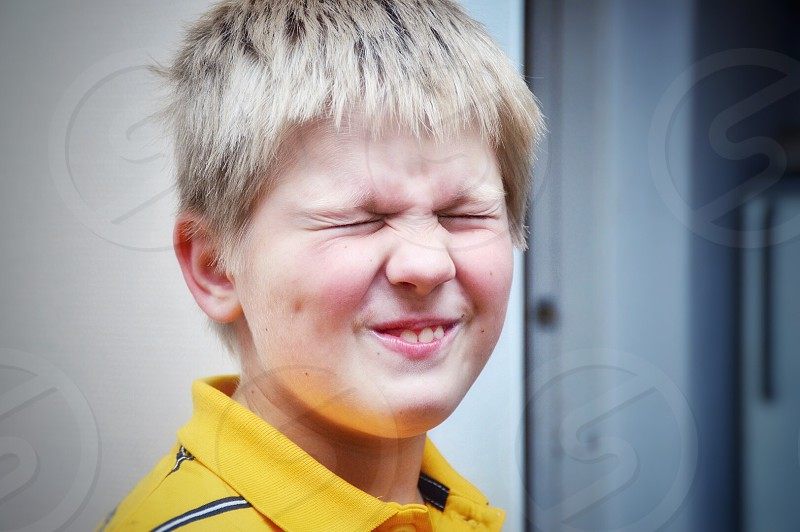 boy wearing yellow black and white striped polo shirt during daytime photo