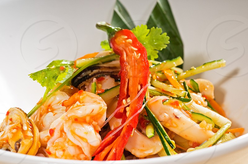 fresh seafood thai style salad with glass noodles on a bowl close up photo