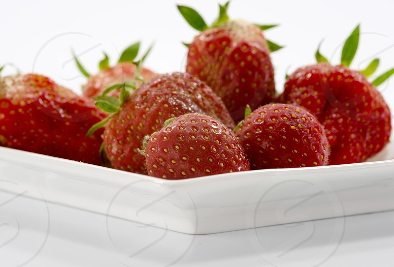 fresh strawberries on white plate photo