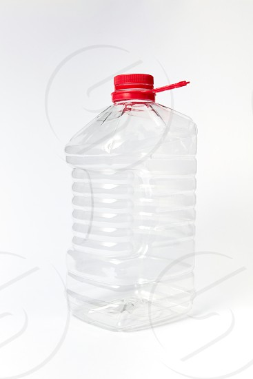 Plastic transparent big container for water dairy and other liquid with red cover on a light gray background copy space. Mock up. photo