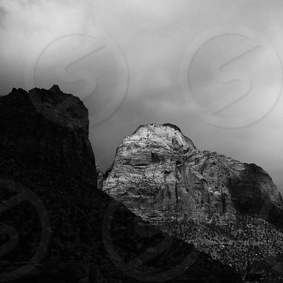 During a storm in Zion National Park Utah harsh shafts of light through the clouds left one peak in perfect brightness and the other in dark shadow. photo