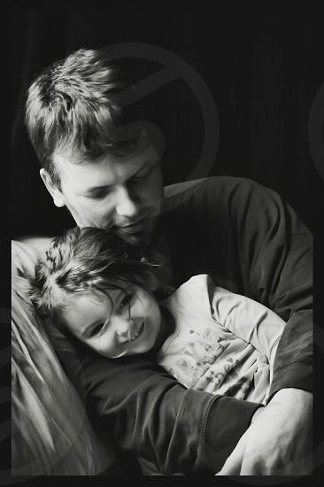 grayscale photo of man hugging girl photo