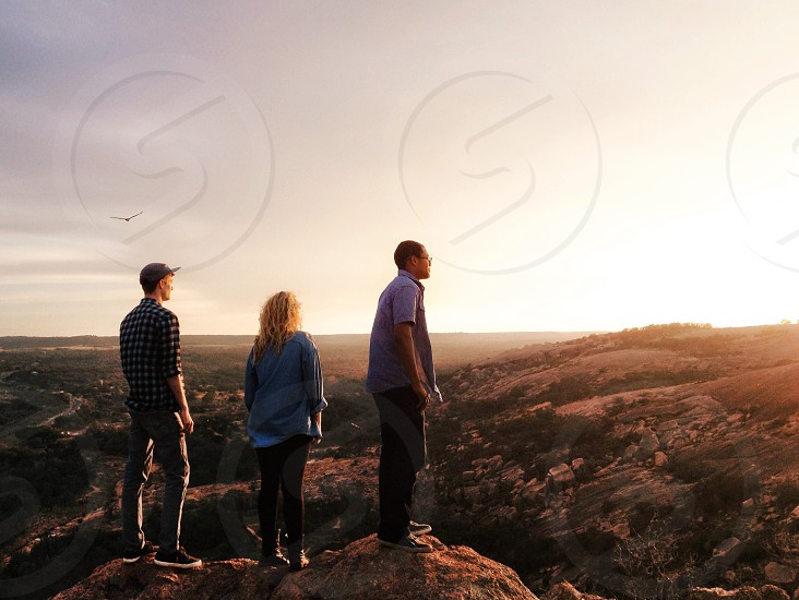 group of people standing on rock looking at mountains photo