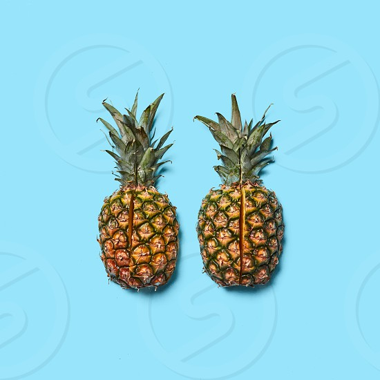Two pineapple halves cut on a blue background with space for text. Tropical healthy fruit. Flat lay photo